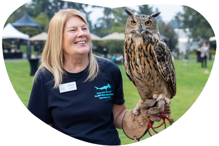 A zookeeper smiles while holding an owl on her arm.