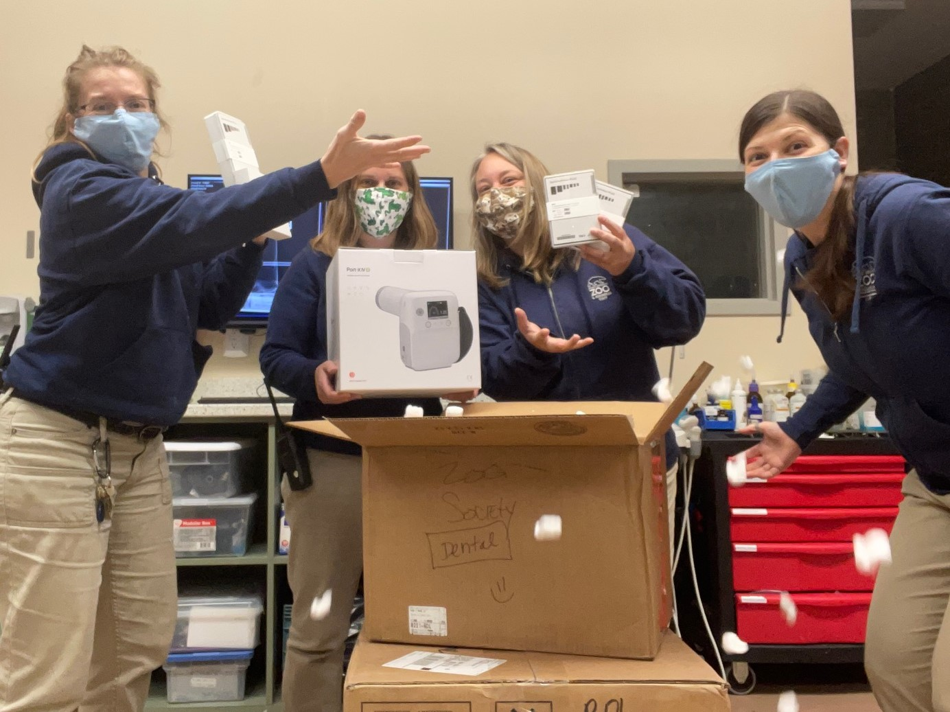 Employees at the Point Defiance Zoo hold up parts of the new dental x-ray machine they acquired.
