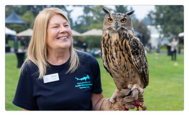 A zookeeper smiles while holding an owl on her arm.A zookeeper smiles while holding an owl on her arm.