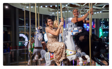 Women dressed in formal attire ride a carousel.