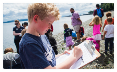 A young teenage fills out a form while standing on a beach amongst a crowd of all ages.