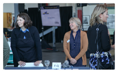 Two women oversee a table at an event.